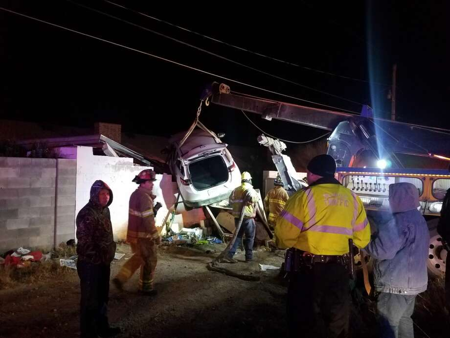 Emergency personnel respond to a wreck that resulted in a vehicle landing on top of a shed. Photo: Mercedes Cordero/Reporter-Telegram