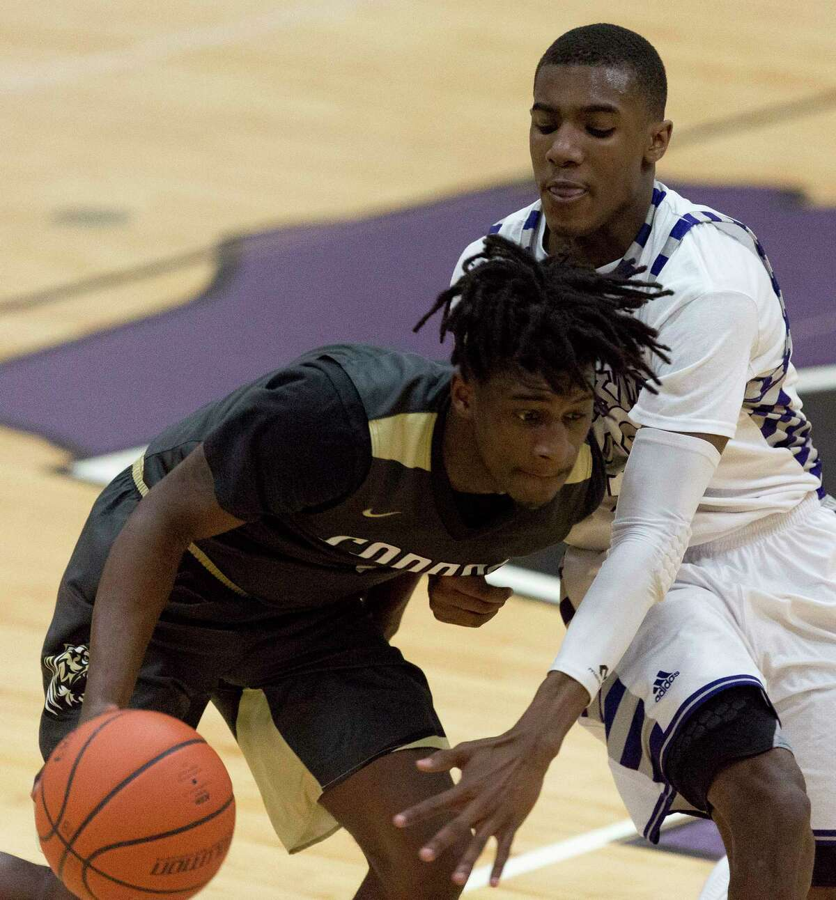 Willis guard Darius Mickens (22) goes up against Conroe guard Jay Lewis (1) during the third quarter of a non-district high school boys basketball game at Willis High School, Tuesday, Jan. 2, 2017, in Willis.