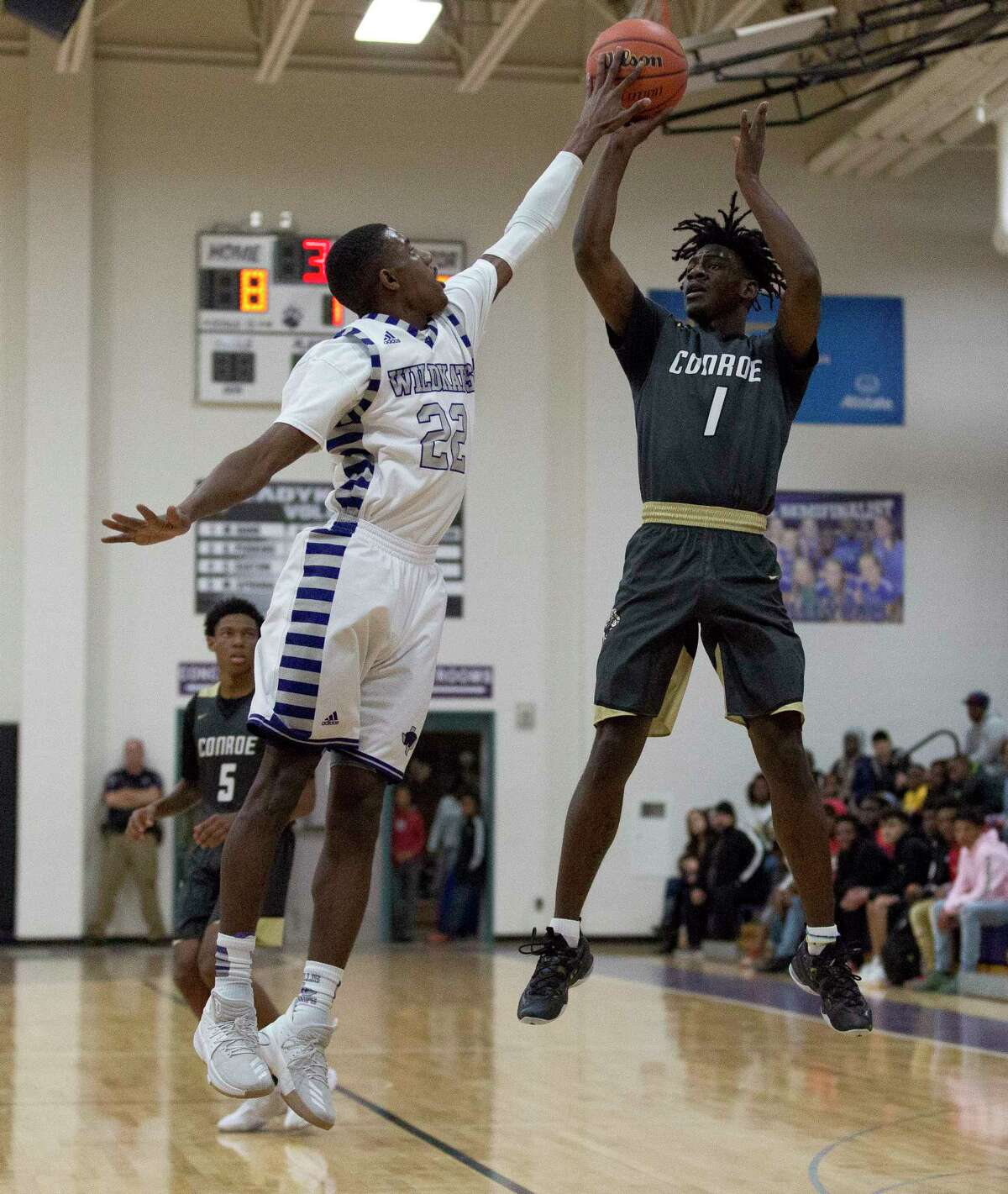 Willis guard Darius Mickens (22) blocks a shot by Conroe guard Jay Lewis (1) during the first quarter of a non-district high school boys basketball game at Willis High School, Tuesday, Jan. 2, 2017, in Willis.