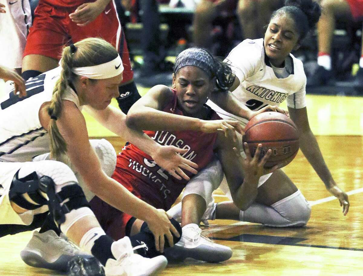 Desiree Lewis fights on the court for a loose ball between Knight players Taylor Skurka (left) and Desiree Caldwell as Steele hosts Judson in girls basketball on January 2, 2018