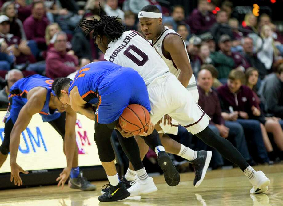 Florida guard Chris Chiozza (11) and Texas A&M guard Jay Jay Chandler (0) fight for a loose ball during the second half of an NCAA college basketball game Tuesday, Jan. 2, 2018, in College Station, Texas. (AP Photo/Sam Craft) Photo: Sam Craft, Associated Press / AP