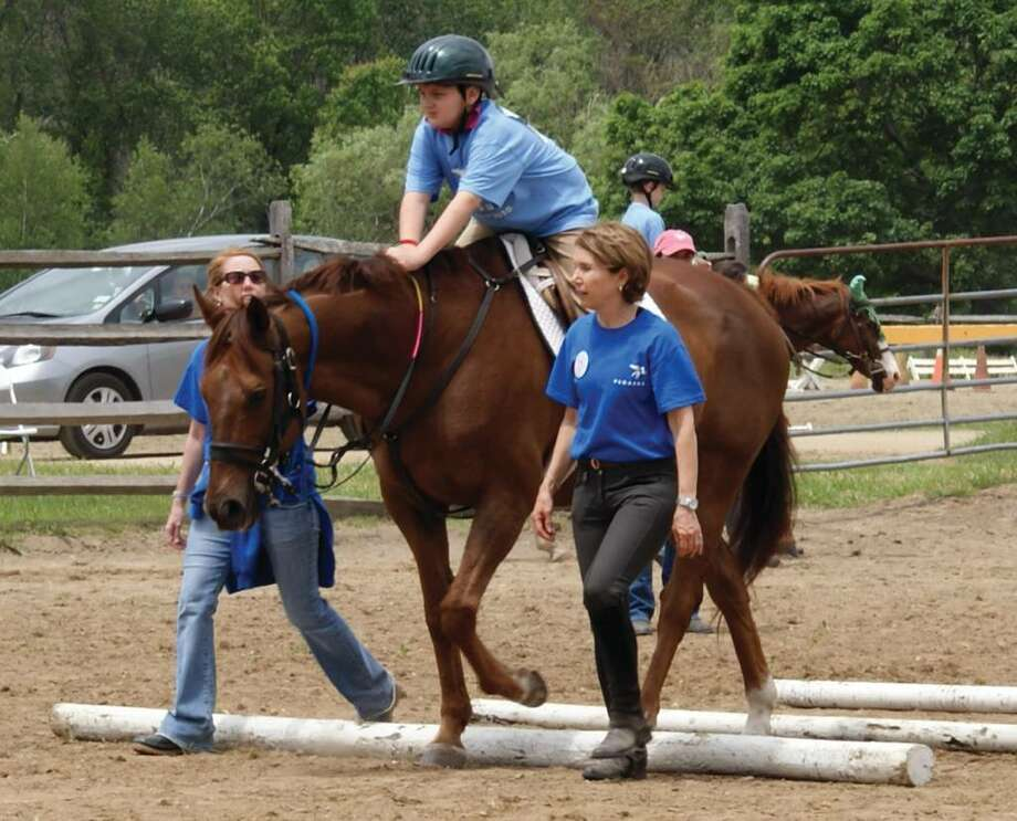 Ned Cowden of Westport steers his therapy horse, CJ, over a set of poles while in the half-seat position. Ned is accompanied by volunteers Marlene Spahr of Norwalk, left, and Cindy Hurvitz, right, of New Canaan. Photo: Contributed Photo, Christine Fitzgerald / Westport News