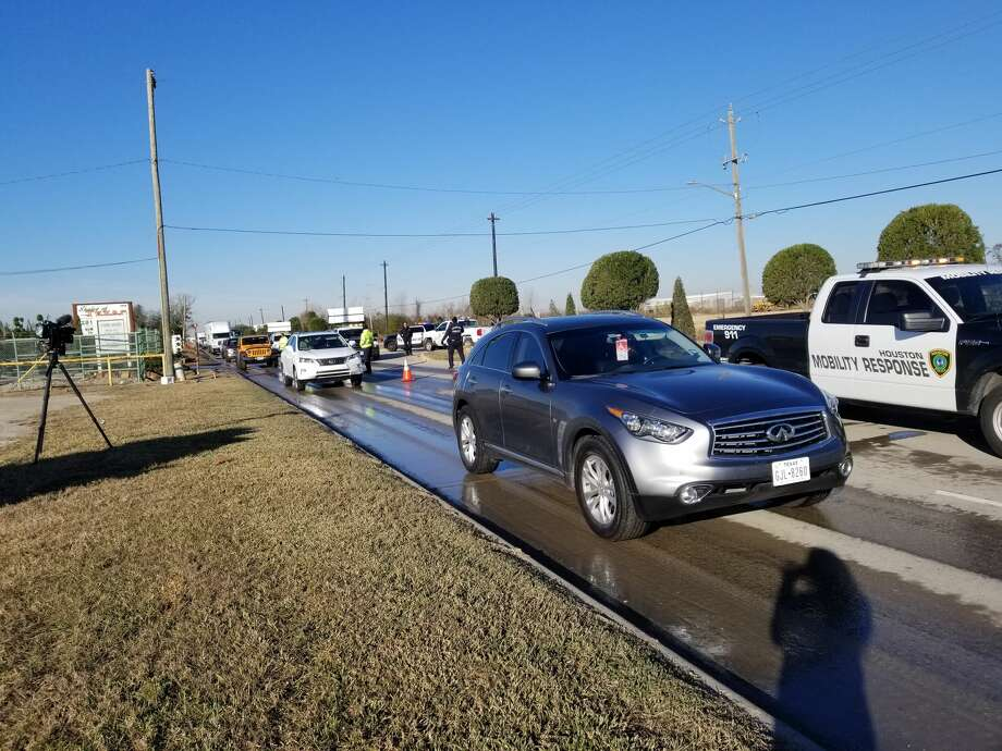 Houston police officers direct drivers to slow down due to ice on the roadway on Genoa Red Bluff on Jan. 3, 2018. Photo: Dana Burke/Houston Chronicle