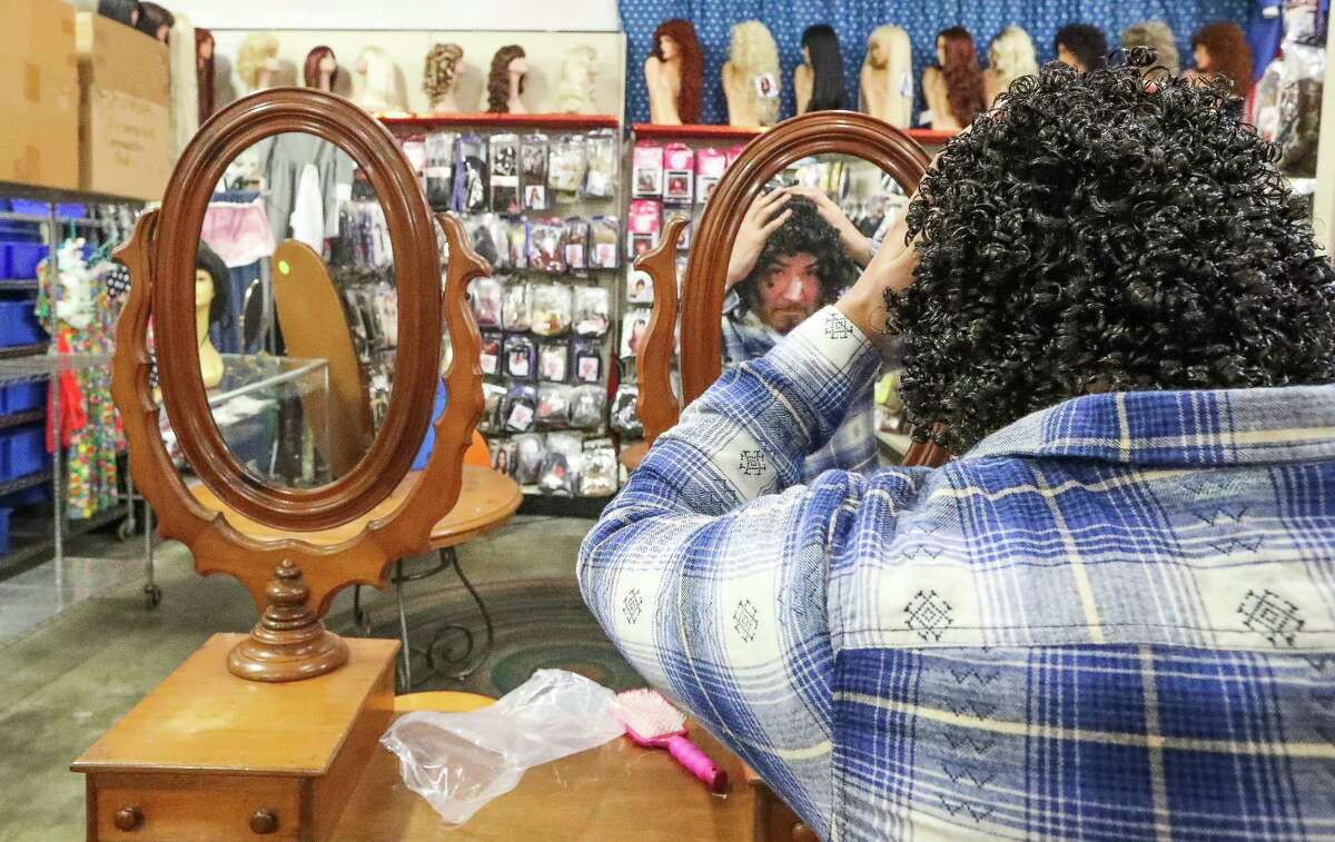 Angel Ramirez tries on a wig at Frankel's, a Houston institution that's closing its doors as the owners are retiring.