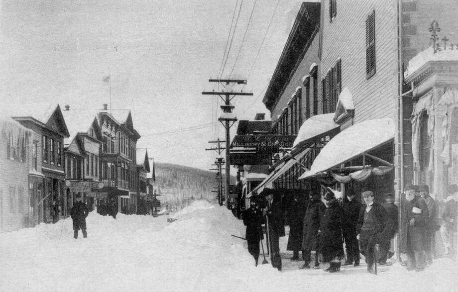 """The intersection of Bank and Main streets in New Milford circa late 19th century was a popular gathering spot shortly after a blizzard had swept through the small farming community. Note some of the men in the photograph are holding or leaning on snow shovels; clearing roads and sidewalk and removing snow without a snowplow was tedious business. If you have a """"Way Back When"""" photo to share, contact Deborah Rose at drose@newstimes.com or 860-3550-7324. Photo: Contributed Photo / Contributed Photo / The News-Times Contributed"""