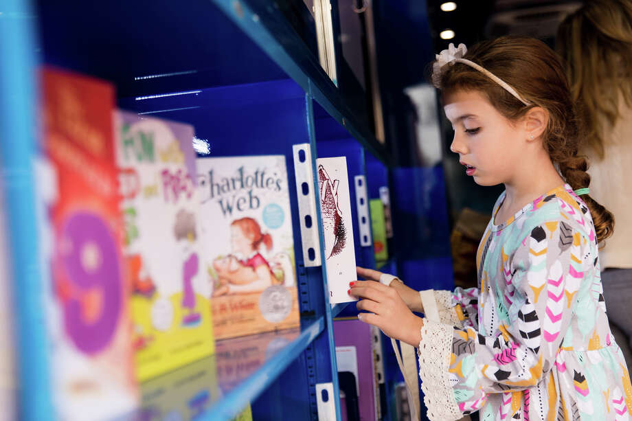 A child examines in the books in the Curiosity Cruiser. Photo: Hung L. Truong Photography, Photographer / © Hung L. Truong Photography