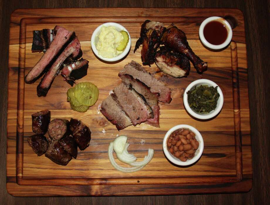 Clockwise from bottom left: house-made beef sausage, pork spare ribs, chicken and beef (brisket). Sides pictured include potato salad, mustard greens and beans at Jones Sausage & Bar-B-Que House at 2827 Martin Luther King Drive. Photo: Chuck Blount / San Antonio Express-News