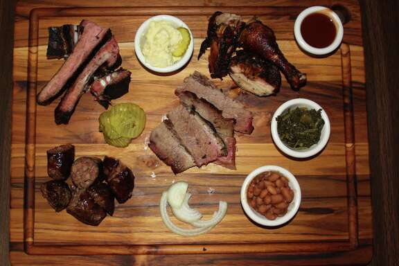 Clockwise from bottom left: house-made beef sausage, pork spare ribs, chicken and beef (brisket). Sides pictured include potato salad, mustard greens and beans at Jones Sausage & Bar-B-Que House at 2827 Martin Luther King Drive.