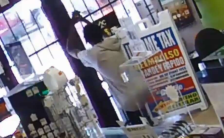 John Bell, 22, pleaded guilty in this April 17 cell phone robbery in December 2017. In surveillance video released Jan. 3, 2018, Bell can be seen pleading for mercy after a store employee escapes and locks Bell in the store until police arrive. Photo: Houston Police Robbery Division