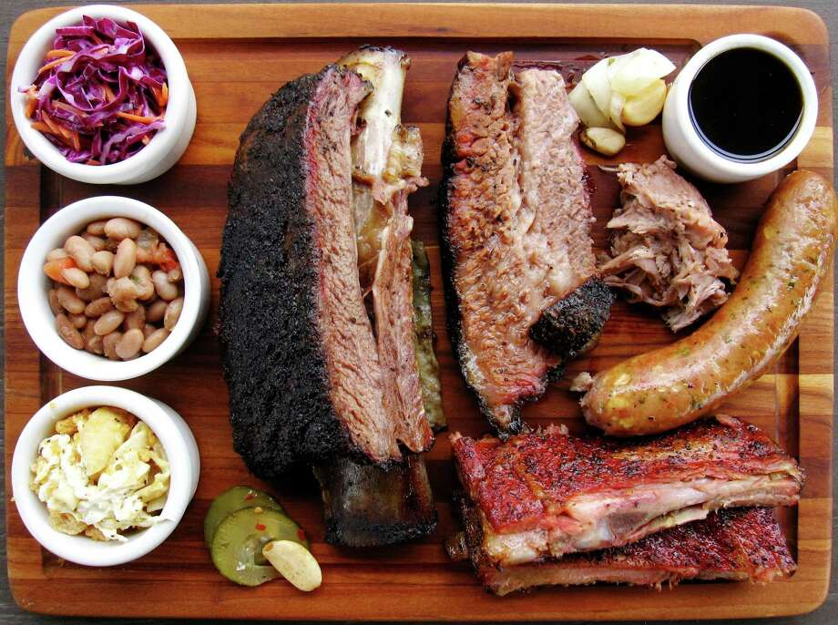 A cutting board full of barbecue and sides from 2M Smokehouse, including brisket, pork ribs, sausage, pulled pork, a beef rib, cole slaw, beans and chicharrón mac and cheese. Photo: Mike Sutter /San Antonio Express-News