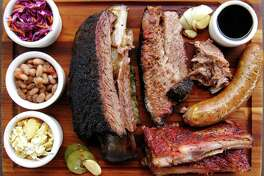 Barbecue and sides from 2M Smokehouse, including brisket, pork ribs, sausage, pulled pork, a beef rib, cole slaw, beans and chicharrón mac and cheese.
