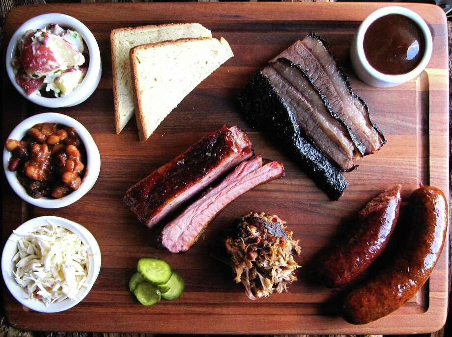 Barbecue and sides from The Granary 'Cue & Brew, including, clockwise from bottom left, cole slaw, burnt-end baked beans, potato salad, buttermilk bread, brisket, sauce, sausage, pulled pork and pork ribs. Photo: Mike Sutter /San Antonio Express-News