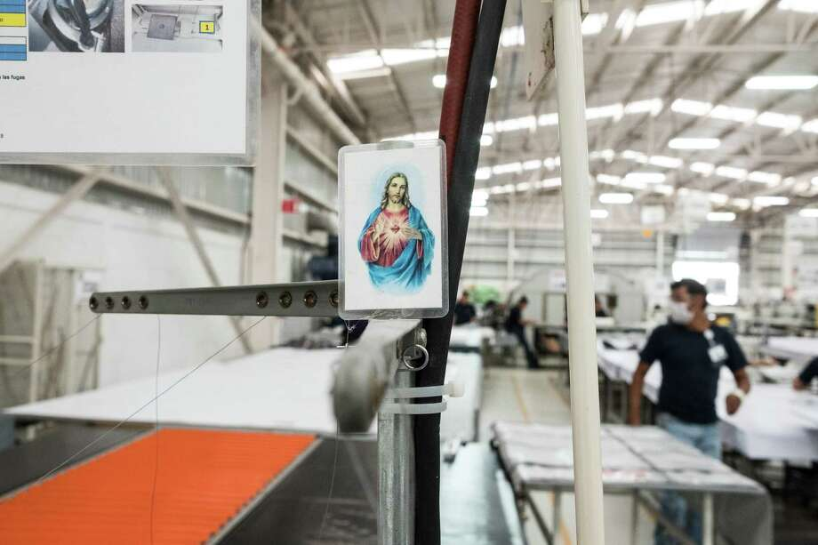 A catholic prayer card is seen at a workstation inside the Tighitco Inc. manufacturing facility in San Luis Potosi, Mexico, on Thursday, Nov. 16, 2017. With 312 registered industrial facilities and close to 50,000 jobs created to date, the aerospace sector is one of the fastest growing in the country with a 15% average annual growth. The US represents 79 percent of Mexico's total exports, followed by Canada with 7 percent, according to the President of the Mexican Federation for the Aerospace Industry (FEMIA) Carlos Robles. Photographer: Maurico Palos/Bloomberg Photo: Maurico Palos, Bloomberg / © 2017 Bloomberg Finance LP