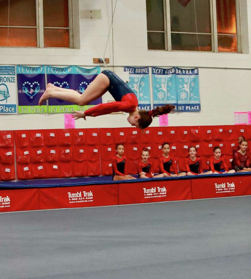 With her teammates cheering her on, Darien YMCA Level 6 gymnast Anna Altier (New Canaan) flipped to a huge 9.4 score to win the floor title at the New England Invitational. Photo: Contributed Photo / Darien News contributed
