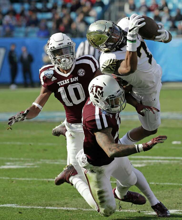 Wake Forest's Scotty Washington (7) catches a pass as Texas A&M's Larry Pryor (11) and Myles Jones (10) defend during the first half of the Belk Bowl NCAA college football game in Charlotte, N.C., Friday, Dec. 29, 2017. (AP Photo/Chuck Burton) Photo: Chuck Burton, STF / Copyright 2017 The Associated Press. All rights reserved.