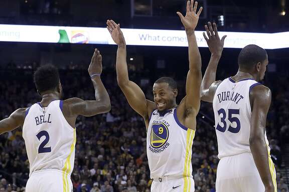 Golden State Warriors forwards Jordan Bell (2), Andre Iguodala (9) and Kevin Durant (35) celebrate during the second half of the team's NBA basketball game against the Utah Jazz in Oakland, Calif., Wednesday, Dec. 27, 2017. The Warriors won 126-101. (AP Photo/Jeff Chiu)
