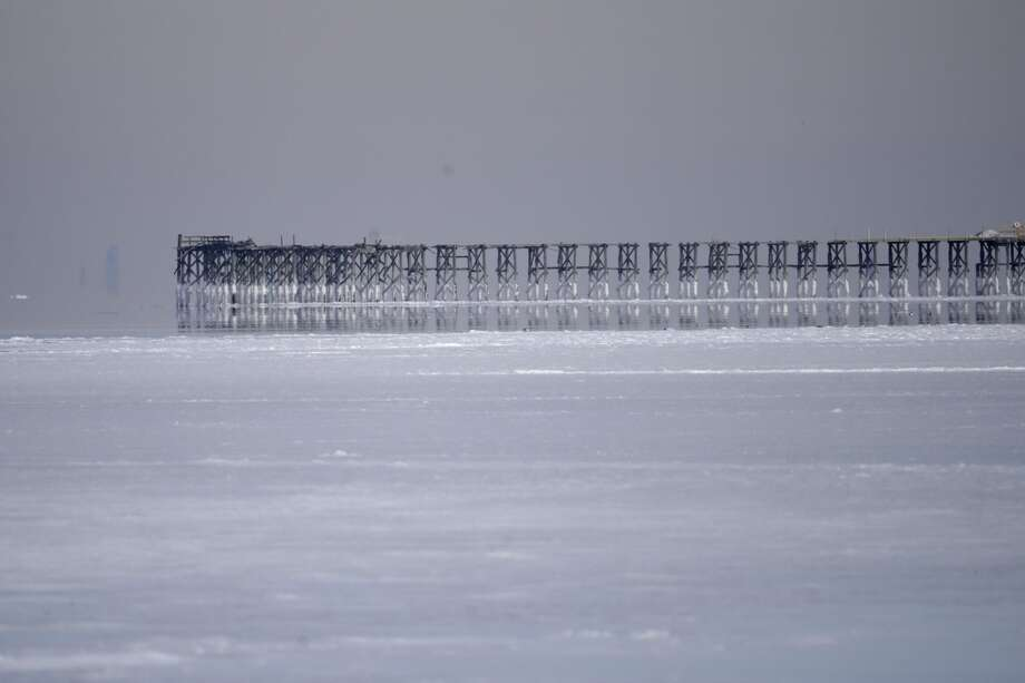 A large layer of ice covers the water along the shore of the Raritan Bay near the pier at Jersey Shore Beach and Boardwalk, Wednesday, Jan. 3, 2018, seen from Union Beach, N.J. The New Jersey Shore, which has been experiencing deep cold weather, is gearing up for a winter storm that forecasters say will bring several inches of snow on Thursday. (AP Photo/Julio Cortez) Photo: Julio Cortez/AP