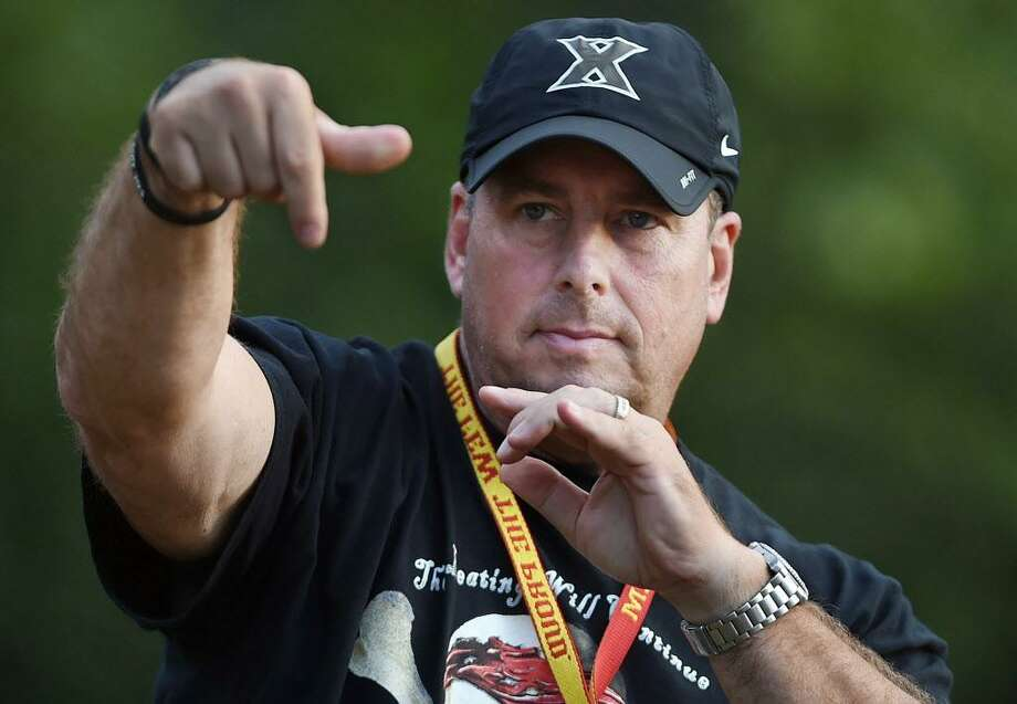 Xavier High School head football coach, Sean Marinan tosses the football at practice in this archive photograph. Photo: File Photo / The Middletown Press