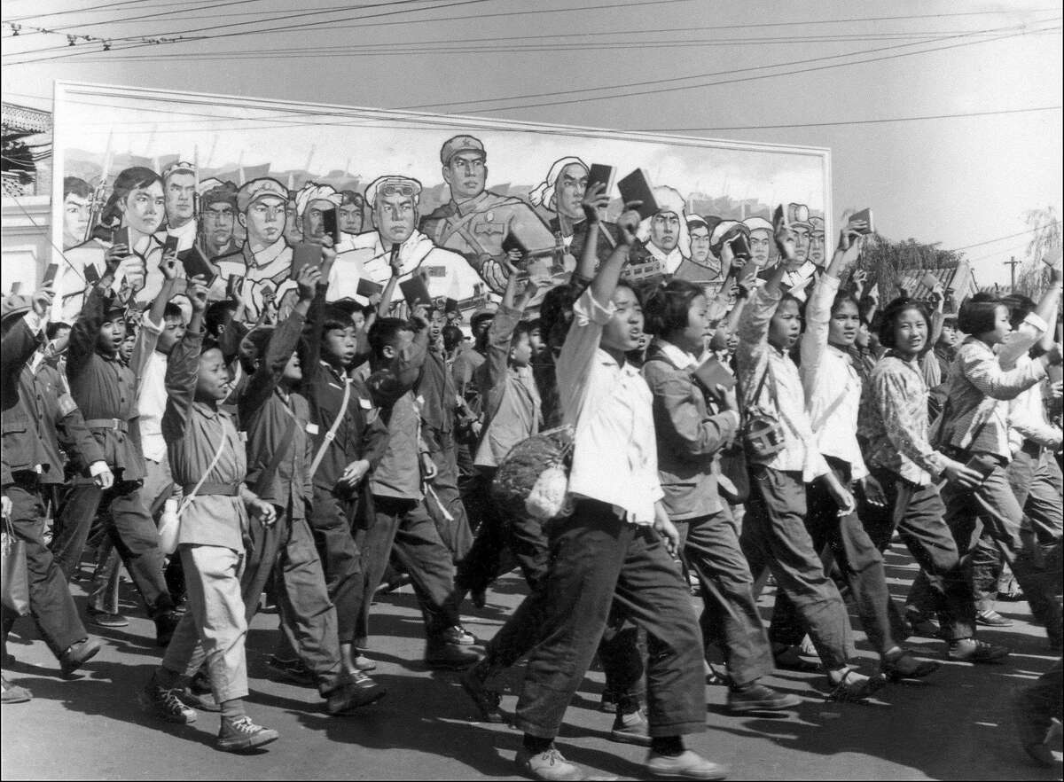 """TO GO WITH STORY """"AFPLIFESTYLE-CHINA-RELIGION-CULTURE"""" (FILES) This file photo dated June, 1966 shows Chinese Red Guards, high school and university students, waving copies of Chairman Mao Zedong's """"Little Red Book,"""" parade in Beijing's streets at the beginning of the Great Proletarian Cultural Revolution. During China's Cultural Revolution of 1966 to 1976, when at the command of Mao Zedong, one of the 20th century's most tyrannical dictators, Red Guards rampaged through much of the country, pillaging cultural symbols that were deemed as not representative of communist heroes Mao and Marx. AFP PHOTO/FILES (Photo credit should read JEAN VINCENT/AFP/Getty Images)"""