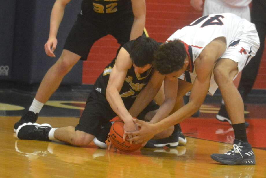Plainview's Josh Thomas, right, fights for possession of the basketball with an Amarillo High player during a game at the Dog House Tuesday night. Amarillo defeated the Bulldogs, 65-50, in District 3-5A play. Photo: Skip Leon/Plainview Herald