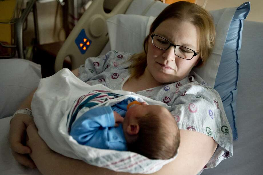 Jessica McClain holds her newborn son, Kris Gerald McClain, on Wednesday, Jan. 3, 2018 at MidMichigan Medical Center-Midland. Kris was born to parents Jessica and Davin McClain on Tuesday, Jan. 2 at 7:44 a.m. and is the first Midland baby born in 2018. (Katy Kildee/kkildee@mdn.net) Photo: (Katy Kildee/kkildee@mdn.net)