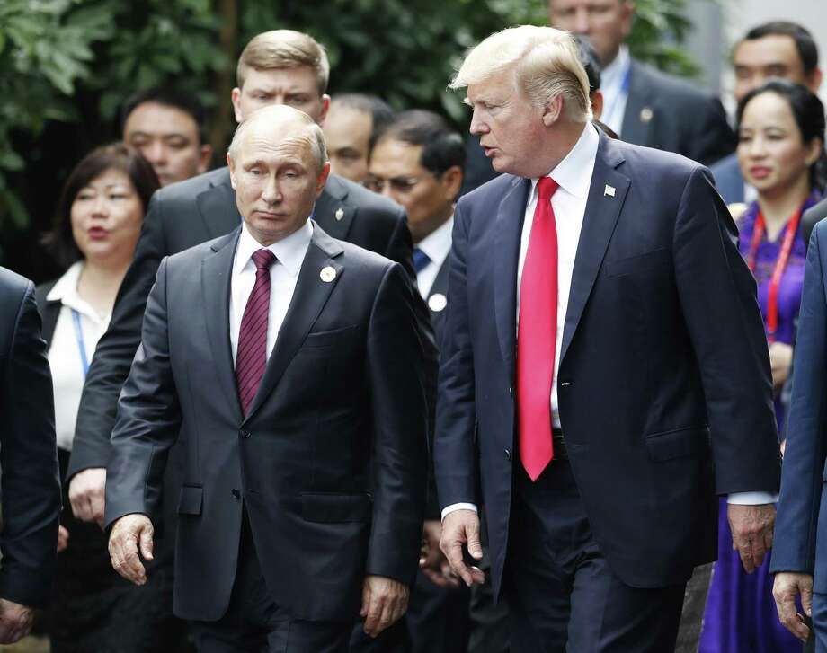 U.S. President Donald Trump, right, and Russia's President Vladimir Putin talk during the family photo session at the APEC Summit in Danang, Vietnam Saturday, Nov. 11, 2017. Trump and Putin may not be having a formal meeting while they're in Vietnam for an economic summit. But the two appear to be chumming it up nonetheless. Snippets of video from the Asia-Pacific Economic Cooperation conference Saturday have shown the leaders chatting and shaking hands at events including a world leaders' group photo. (Jorge Silva/Pool Photo via AP) Photo: Jorge Silva / Associated Press / Pool Reuters
