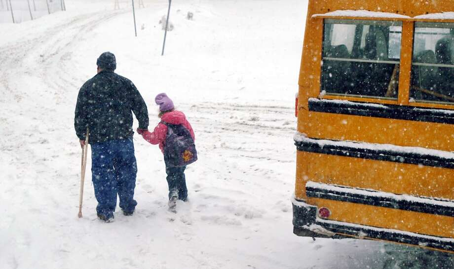 A 2003 snow storm took the Stamford school system by surprise, causing buses to be late and prompting an early dismissal. Here, William Marquet holds his daughter Rachel's hand as he brings the first-grader home early from Stark Elementary School. Photo: ANDREW SULLIVAN / FILE PHOTO / SCNI