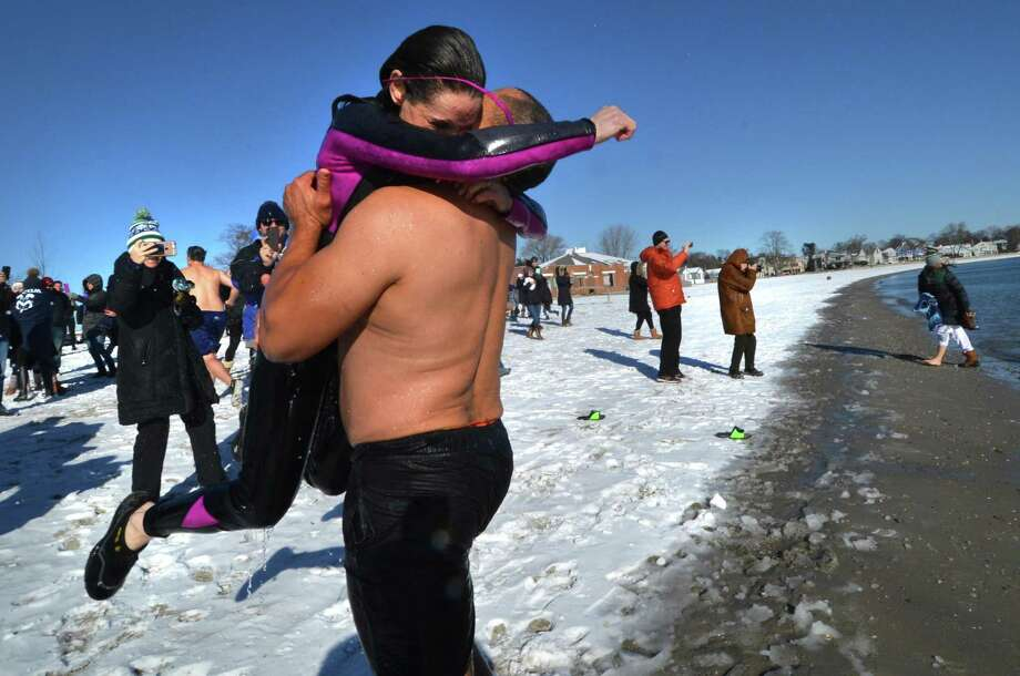 Jill Rutsky, wife of the late Scott Rutsky, gets a hug from event organizer Tom Patterson as they leave the water during the 11th annual Temple Israel Polar Bear Plunge at Compo Beach in Westport on Monday. This year's event was in honor of Scott, who passed away last year and was a major contributor to various charities. Photo: Alex Von Kleydorff / Hearst Connecticut Media / Norwalk Hour