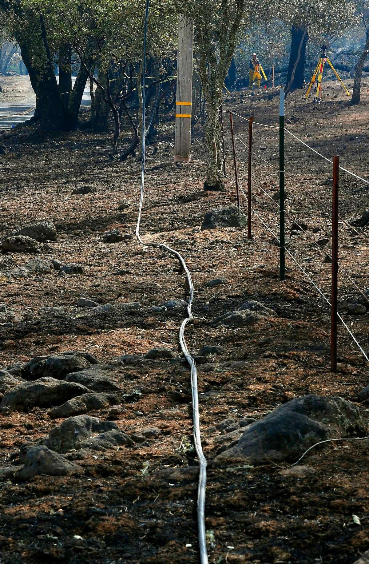 Burned power lines on the ground as investigators (background) searched for the cause of the Atlas fire east of Santa Rosa, Ca. as seen on Tuesday October 17, 2017.