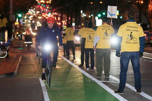 """Demonstrators form a """"people protected bike lane"""" as they protest the city's slowness in installing a real protected bike lane at one of the city's most dangerous intersections on Monday, December 4, 2017 in San Francisco, Calif."""