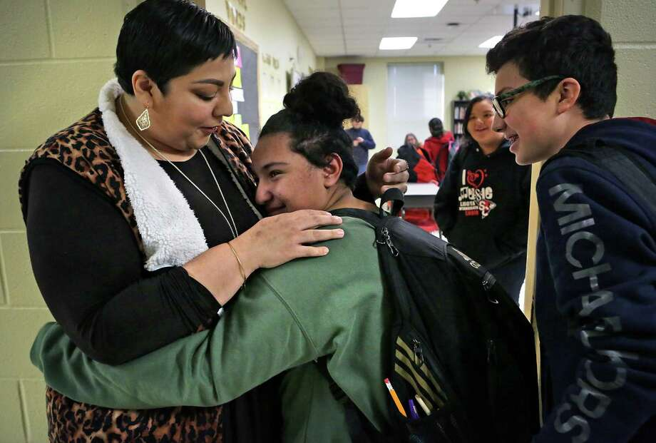 Alicia San Miguel, left, a 6th grade teacher at Losoya Intermediate School who was injured in a car accident back in September, is greeted by a tearful Reinna Harris with a hug as Joel Pichler, right, looks on.  Students in all of San Miguel's classes greeted her on Wednesday, Jan. 3, 2017, her first day back to work since the accident. Photo: Bob Owen, Staff / San Antonio Express-News / ©2017 San Antonio Express-News