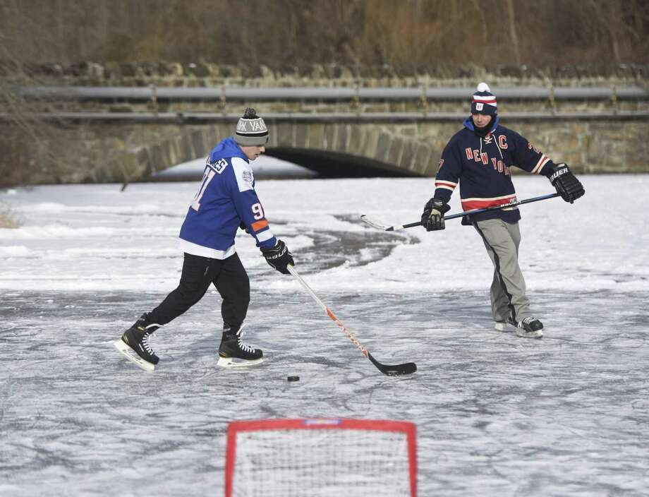 Greenwich residents Alex Loparco, left, and Michael Genaro play hockey on the frozen Mianus River in Greenwich on Wednesday. Despite warning signs, many locals have taken to the river with the recent cold weather for ice skating, fishing and skiing. Photo: Tyler Sizemore / Hearst Connecticut Media / Greenwich Time