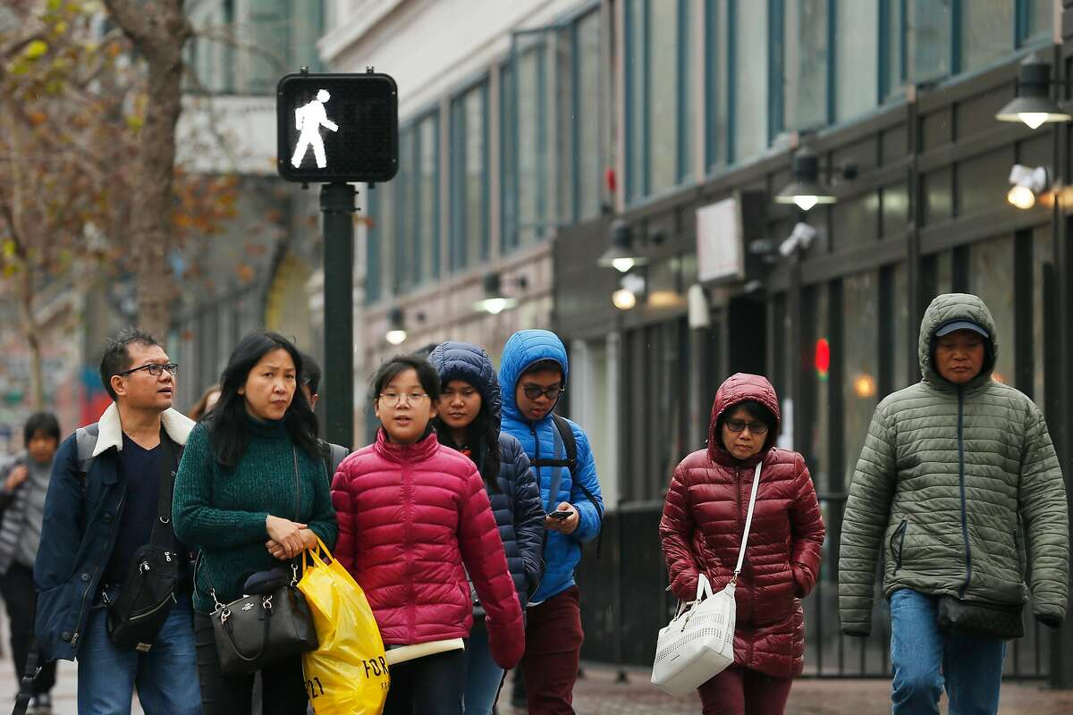 Pedestrians cross the street at Market and 6th streets, Wednesday, Jan. 3, 2018, in San Francisco, Calif.