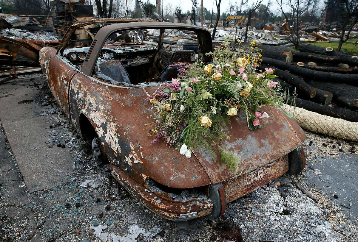 Wilting flowers are left on a charred and rusty Porsche 911 parked on View Court before a visit by Kirstjen Nielsen, Secretary of the Department of Homeland Security, for a tour of the Coffey Park neighborhood destroyed in the Tubbs Fire in Santa Rosa, Calif. on Wednesday, Jan. 3, 2018.
