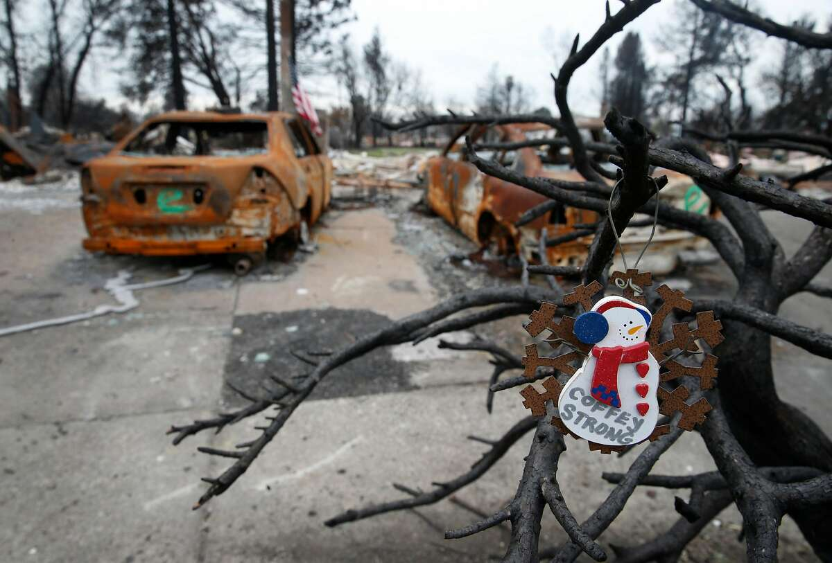 A Christmas ornament hangs from a scorched tree on View Court before a visit by Kirstjen Nielsen, Secretary of the Department of Homeland Security, for a tour of the Coffey Park neighborhood destroyed in the Tubbs Fire in Santa Rosa, Calif. on Wednesday, Jan. 3, 2018.