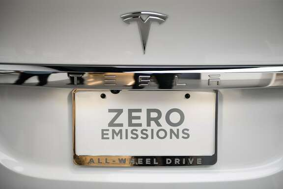 "A ""Zero Emissions"" tag is seen on the rear of a Tesla Inc. Model X P100D sports utility vehicle (SUV) at the company's new showroom in New York, U.S., on Thursday, Dec. 14, 2017. The Meatpacking District location, which opens to the public at 11 a.m. Friday, lets customers for the first time explore energy offerings, configure cars and place orders all under one roof. Photographer: Mark Kauzlarich/Bloomberg"