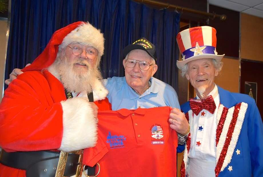 Capital District Patriot Flight hosted Santa and Uncle Sam at their Christmas party at the Gateway Diner. Here they surround World War II Navy veteran Charlie Levesque and his gift. (Submitted photo)