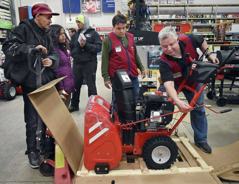 Lowe's employees Jacek Zielimski, at right, and Vinny Torfason set up a Troy-bilt snowblower for Carlos Ortiz, Jadin Ortiz and Lou Mateo, at the home improvement chain at 115 Foxon Blvd. in New Haven, Wednesday, Jan. 3, 2018. Photo: Catherine Avalone, Hearst Connecticut Media / New Haven Register