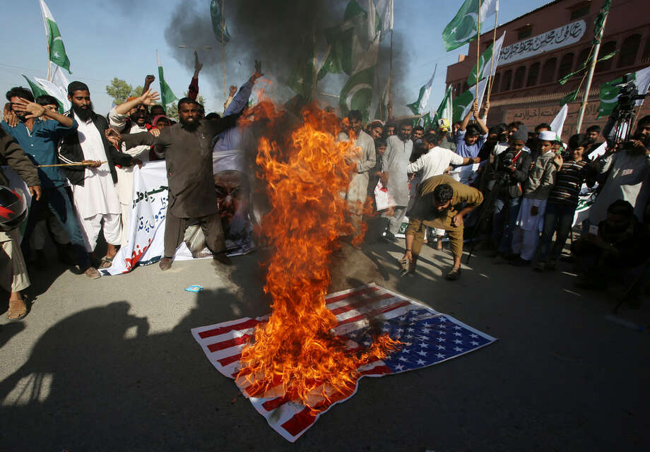 Supporters of Pakistani religious groups burn a representation of an American flag at a rally to condemn a tweet by U.S. President Donald Trump, in Karachi, Pakistan, Tuesday, Jan. 2, 2018. Trump slammed Pakistan for 'lies & deceit' in a New Year's Day tweet that said Islamabad had played U.S. leaders for 'fools'. 'No more,' Trump tweeted. (AP Photo/Fareed Khan)