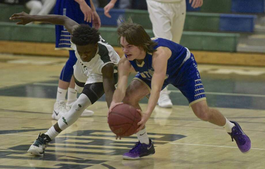 New Milford's Malik Proctor (0) and Newtown's Riley Ward (11) fight for a loose ball in the boys basketball game between Newtown and New Milford high schools, on Wednesday night, January 3, 2018, at New Milford High School, in New Milford, Conn. Photo: H John Voorhees III / Hearst Connecticut Media / The News-Times