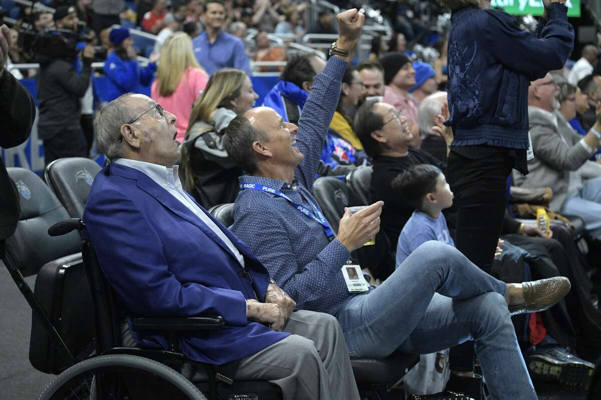Orlando Magic owner Rich DeVos, left, and his son, Amway president Doug DeVos, center, react while watching from their court side seats during the first half of an NBA basketball game against the Houston Rockets Wednesday, Jan. 3, 2018, in Orlando, Fla. (AP Photo/Phelan M. Ebenhack)