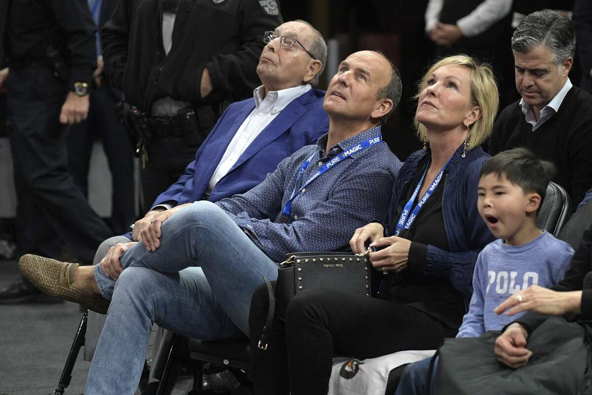 Orlando Magic owner Rich DeVos, left, his son, Amway president Doug DeVos, center, and daughter-in-law, Maria DeVos, watch from their court side seats during the first half of an NBA basketball game against the Houston Rockets Wednesday, Jan. 3, 2018, in Orlando, Fla. (AP Photo/Phelan M. Ebenhack)