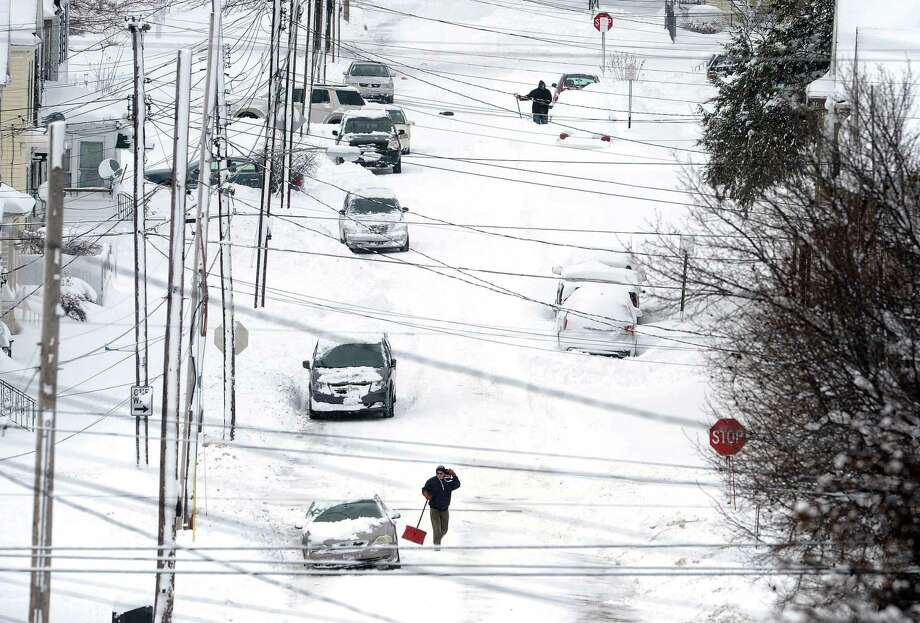Erie, Pa., residents on East 24th Street dig out on Tuesday, Dec. 26, 2017, after a record two-day snowfall. The National Weather Service office in Cleveland says the storm brought 34 inches on Christmas Day, a new all-time daily snowfall record for Erie. (Greg Wohlford/Erie Times-News via AP) Photo: Greg Wohlford, MBI / Erie Times-News