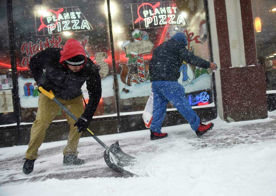 Planet Pizza employees Fabian Zavala, left, and Carlos Compos shovel and salt the sidewalk outside their restaurant as heavy snow falls in Greenwich, Conn. Thursday, Jan. 4, 2018. Snow began early Thursday morning and is continuing throughout the day, coupled with heavy winds and low visibility. Photo: Tyler Sizemore, Hearst Connecticut Media / Greenwich Time