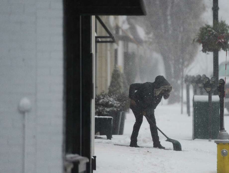 A woman shovels the sidewalk outside Le Pain Quitodien as heavy snow falls in Greenwich, Conn. Thursday, Jan. 4, 2018. Snow began early Thursday morning and is continuing throughout the day, coupled with heavy winds and low visibility. Photo: Tyler Sizemore, Hearst Connecticut Media / Greenwich Time