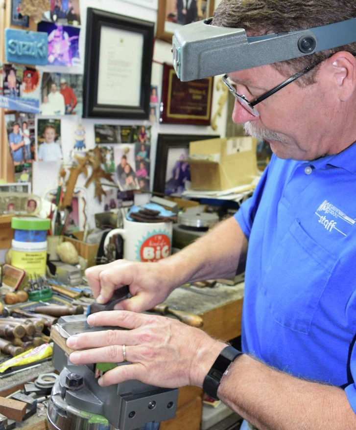 Master Engraver Weldon Lister polishes a plate he just finishing engraving at his shop near Welfare where collectors and those seeking lasting memories of hunts gone by take advantage of his creative skills with a hammer and chisel.
