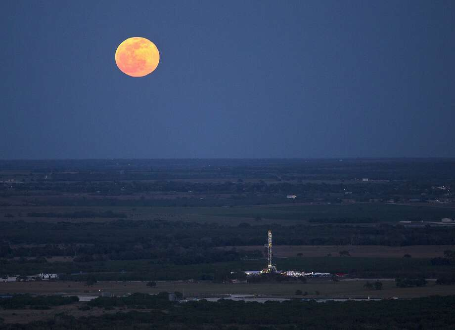 The full moon rises above an oil drilling rig Wednesday, May 14, 2014 in an aerial image taken near Karnes City, Texas. Photo: William Luther, San Antonio Express-News
