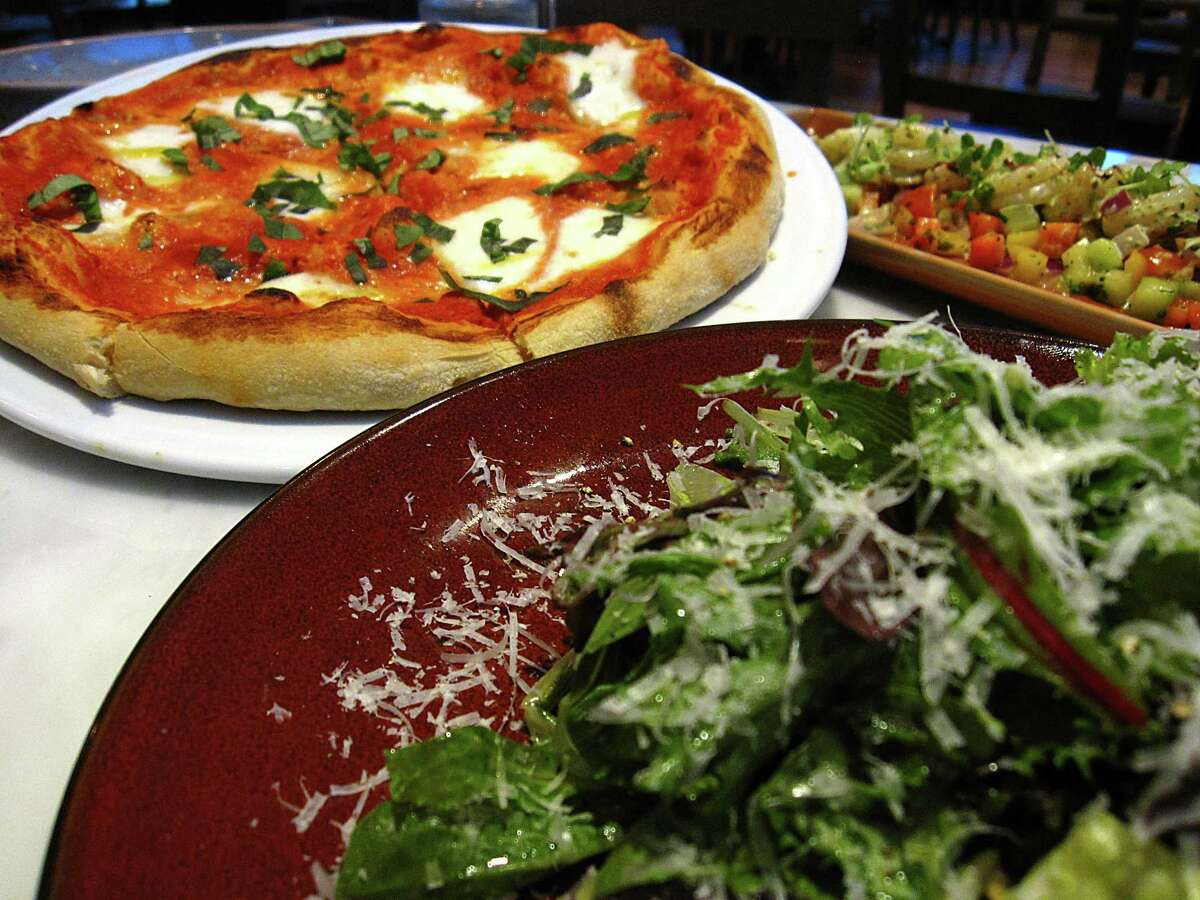 A margherita pizza flanked by an insalata verde and a shrimp salad