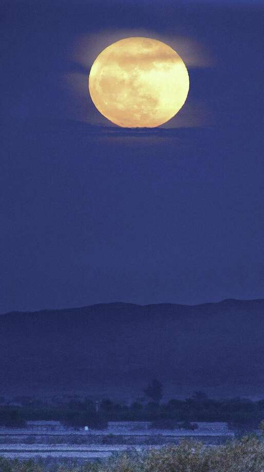 The first full moon of 2018 rises over the Gila Valley, peaking out from behind clouds behind the Muggins Mountains early Monday. Photo: Randy Hoeft / Associated Press / The Yuma Sun