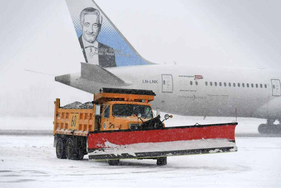 Snow is cleared to make a parking spot for a Norwegian Air Boeing 787-9 Dreamliner that was diverted from JFK to Albany International Airport because of bad weather on Thursday, Jan. 4, 2018, in Colonie, N.Y. The flight originated at London Gatwick. (Will Waldron/Times Union) Photo: Will Waldron, Albany Times Union / 20042563A